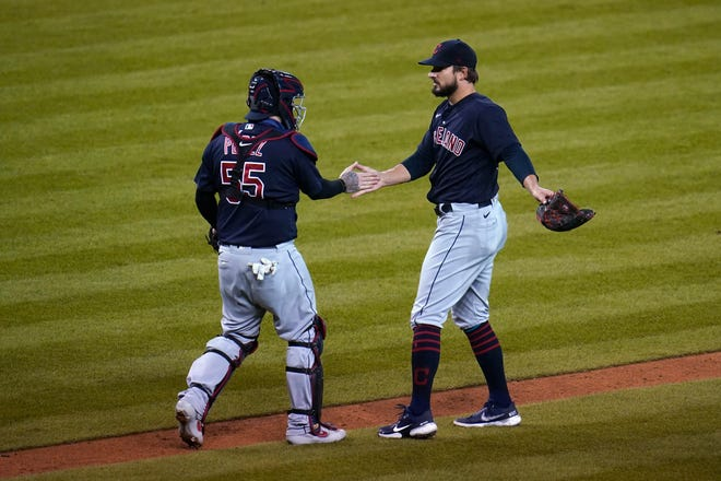 Cleveland Indians catcher Roberto Perez (55) and Brad Hand celebrate after the final out in the ninth inning of a baseball game in Detroit, Friday, Sept. 18, 2020. Cleveland won 1-0. (AP Photo/Paul Sancya)