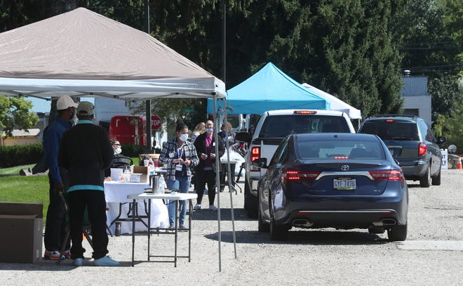 Cars drive to different service organizations at a community outreach event at the House of the Lord on Saturday in Akron. [Mike Cardew/Beacon Journal]