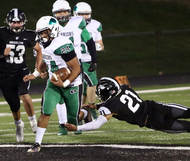 West Branch's Alek Wilson (24) on a long second-quarter run as Carrollton's Domanick Speelman (21) tries to tackle during last Friday's game. Wilson ran the ball well and also led the team with nine pass receptions.