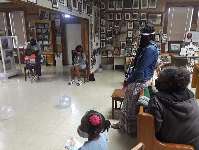 Children learn a lesson about Black history Saturday at the Finding Our Roots African American Museum's reopening.