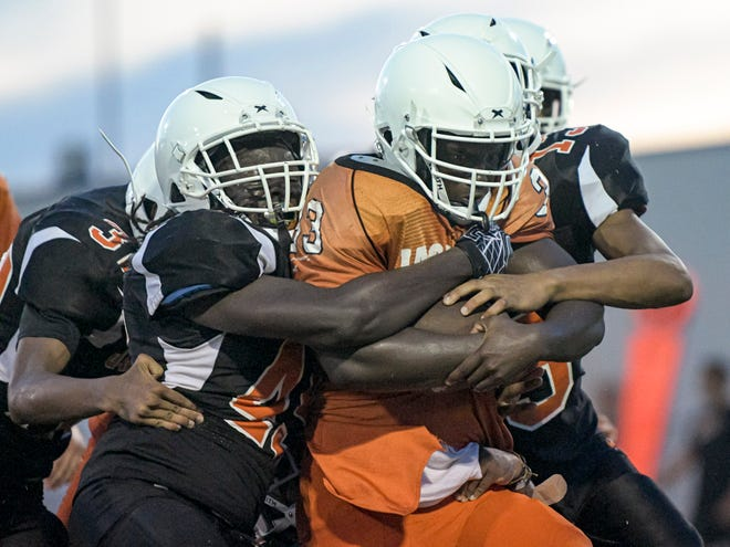 Leesburg's Eric Coffie (33) is gang-tackled at the annual Orange and Black game Friday at H.O. Dabney Stadium at Leesburg High School. [PAUL RYAN / CORRESPONDENT]