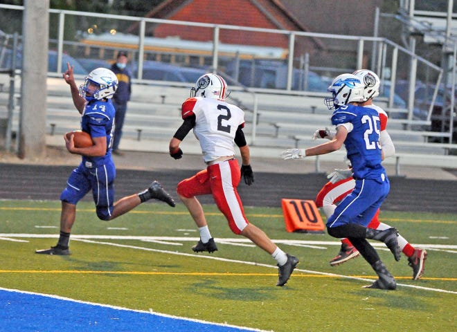 Chippewa quarterback Christian Moyer runs into the end zone for six points as Rittman's Cade Newark closes in.