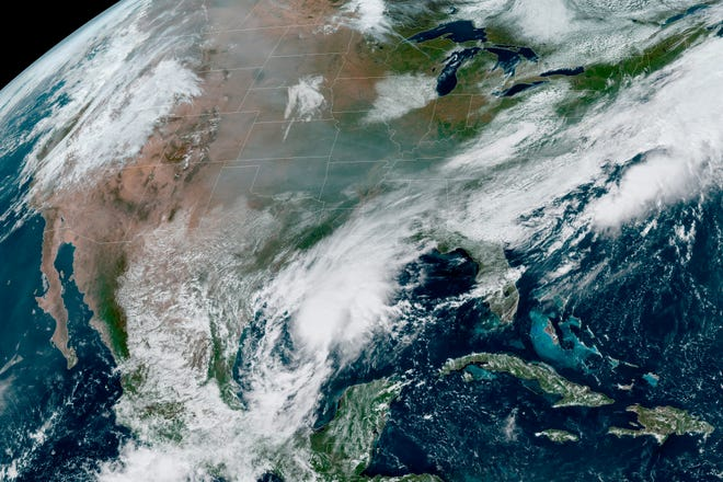 A satellite image made available by the National Oceanic and Atmospheric Administration shows gray smoke from wildfires Friday, Sept. 18, 2020, in the western United States drifting across the continent and the remnants of Hurricane Sally in the southeast.