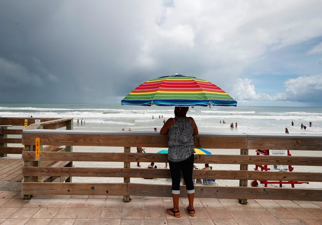 A beachgoer uses an umbrella to protect from the sun and on-and-off showers on the beach in Daytona Beach on Saturday.
