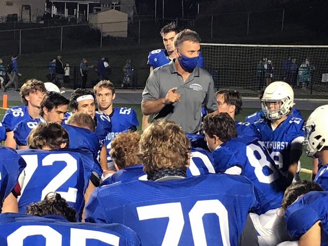 Rockhurst coach Kelly Donohoe (in mask), the former longtime Blue Springs coach, addresses his team following Friday's 36-14 win over Blue Springs South.