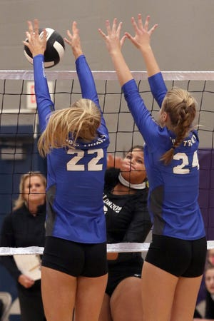 Holy Trinity Crusaders' Katie Denning (22) and Bailey Hellweg (24) successfully block a hit by New London's Keaura Williams during a match at Keokuk Middle School during the Keokuk HS Volleyball Invite Saturday. [Donald K. Aliprandi/thehawkeye.com]