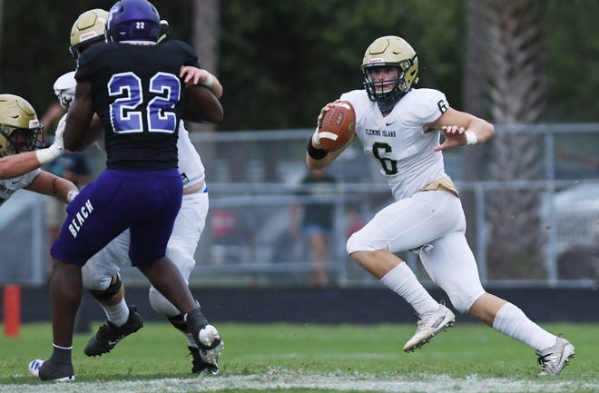Fleming Island quarterback Grant Travis (6) scrambles as Fletcher defensive end Aaron Hester (22) attempts to pursue during a September game.