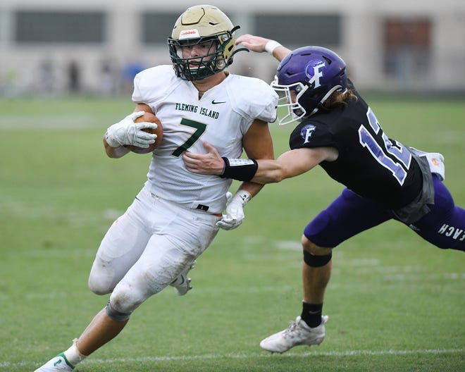Fleming Island running back TK Kocak (7) attempts to escape the tackle of Fletcher safety Merritt Reynolds (12) during a Sept. 18 high school football game.