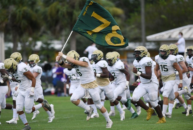 Fleming Island's players charge onto the field before their September game at Fletcher.