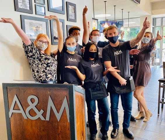 Masked-up staffers celebrate the reopening of Aaron & Moses Restaurant