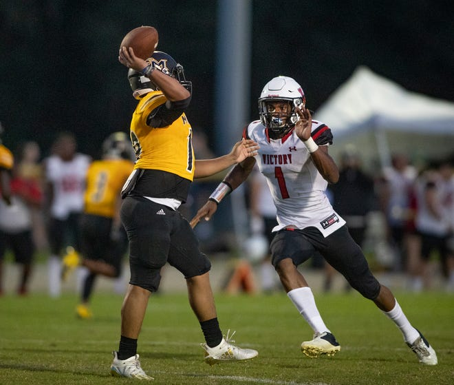 Fort Meade quarterback Rafael Cabrera is challenged by Victory's Dytreyveon Riley at Fort Meade on Sept. 18.