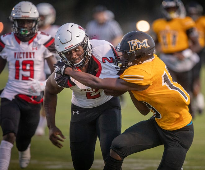 Victory Christian's Cornelius Shaw (2) fends off a tackle by Fort Meade's Chandler White (13) during first-half action at Fort Meade High School on Friday night.