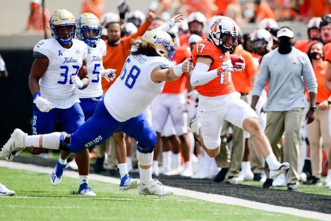 Tulsa defender Deven Lamp (58) chases Oklahoma State wide receiver Dillon Stoner (17) out of bounds in the first half on Saturday in Stillwater, Oklahoma.