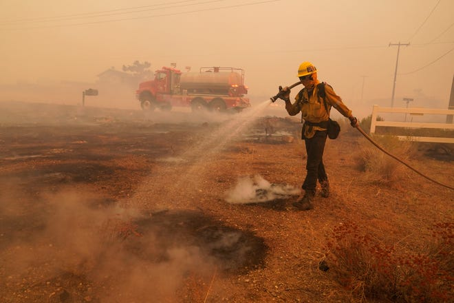 A member of a Los Angeles County Fire crew hoses down hot spots while protecting a home from the advancing Bobcat Fire on Friday in Juniper Hills, Calif.
