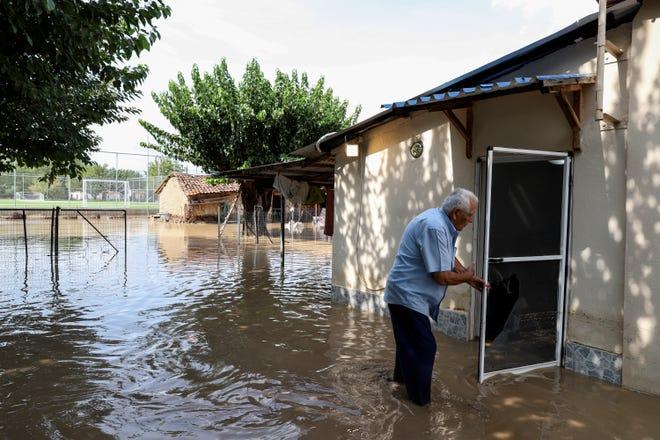 A man tries to enter his flooded home at Magoula village, near Karditsa town, Saturday.
