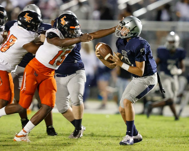 Lake Wales' Terrance Edmonds pressures Ridge quarterback Zachary Pleuss on Friday night at Ridge Community High School.