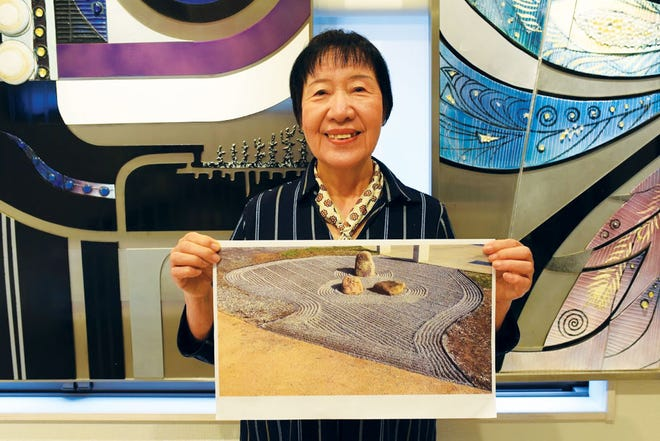 Toshiko Tanaka, an enamel artist who is a Hiroshima survivor, displays the karesansui garden pattern that Martin McKellar raked, based on her design for the 'patterns for peace' project observing the United National International Day of Peace.