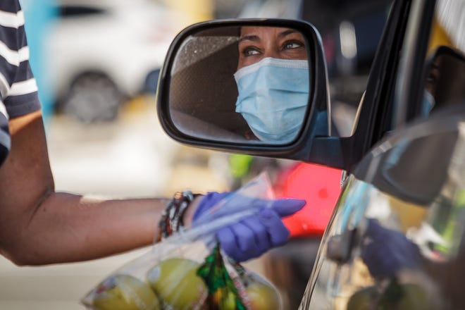 A motorist receives apples at a drive-through Feeding South Florida event Sept. 15 in Lake Worth Beach. Dozens of cars queued on eastbound Lake Avenue to pick up groceries to help during the economic hard times brought on by the COVID-19 outbreak.