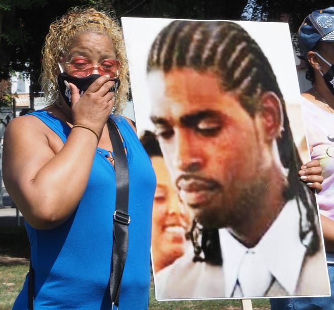 Teresa Spivey holds a picture of her son, Billy Williams, who has served nine years of a 20-year prison sentence for robbery with weapon enhancements, during a pray meeting Saturday at Martin Luther King Jr. Plaza. The family is fighting to have Williams' sentence reduced under SB620, the law that gives judges sentencing discretion when a case has weapon enhancements. Williams was sentenced before passage of the law.