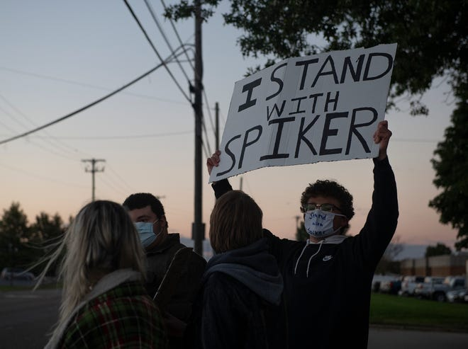 A handful of Rootstown current and former students protest the resignation of head football coach Troy Spiker. Ethan Conroy, holds a sign of support for Spiker.