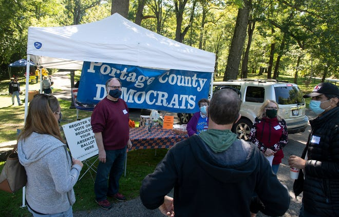 Portage Citizens for Decency organized a drive-thru event to meet the democrat candidates at Fred Fuller Park in Kent. Bob Howard , one of several organizers, including Bob Springer and Fred Mendiola, greets arriving guests.