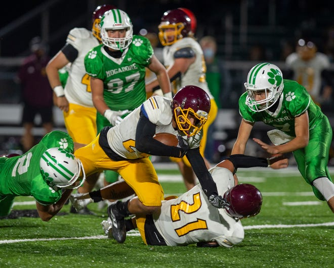 Mogadore hosted Southeast, winning the contest 29-7. Nick Skye holds on to the leg of Jaidyn Sapp. Joe Percy tries to keep defender Kody Jaber back.
