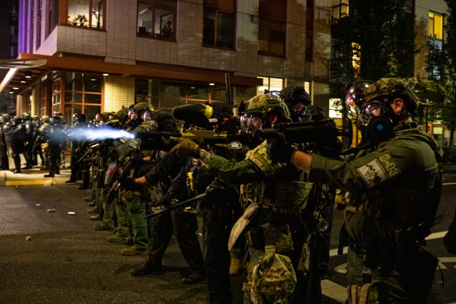 Federal police try to take control of the streets during protests, Friday in Portland. The protests, which began over the killing of George Floyd, often result frequent clashes between protesters and law enforcement.