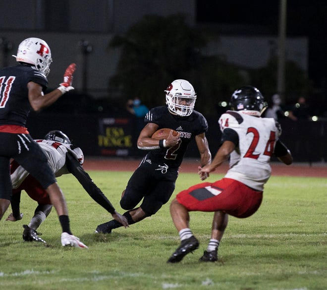 Palmetto High running back Sagel Hickson looks to get around Port Charlotte's Diego Espinoza-Gabaldon Friday night at Harllee Stadium in Palmetto.