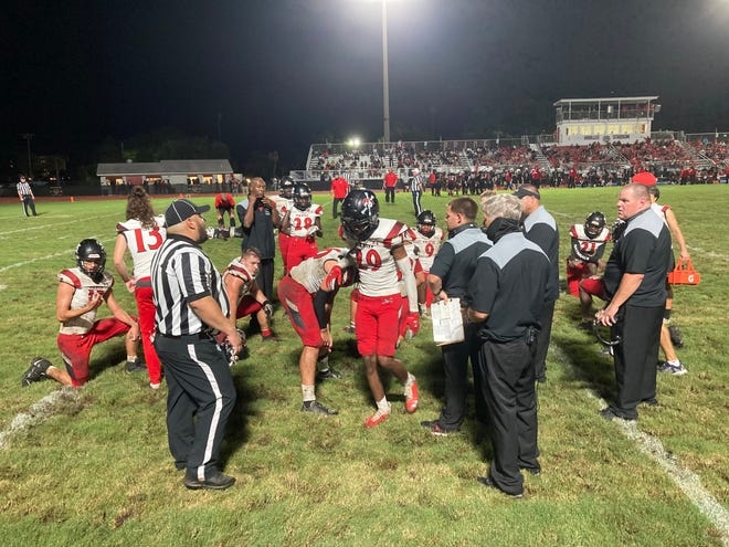 The Port Charlotte High football team gathers near the sideline during its 43-7 loss to Palmetto High on Friday night at Harllee Stadium in Palmetto.