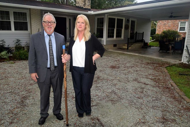 Larry and Jane Swinson hold a four-foot walking stick which shows the depth of 2018's Hurricane Florence flood waters in their Trent Woods home.