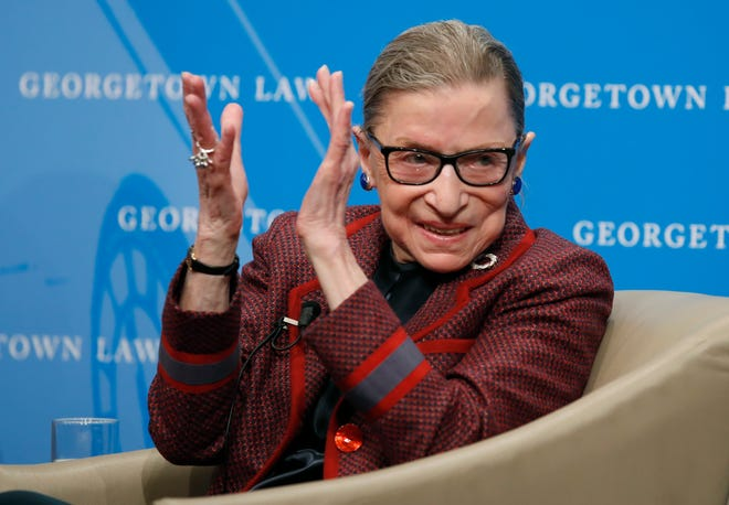 Supreme Court Justice Ruth Bader Ginsburg applauds after a performance in her honor in 2018 after she spoke about her life and work during a discussion at Georgetown Law School in Washington. The Supreme Court says Ginsburg has died of metastatic pancreatic cancer at age 87.