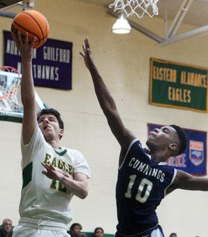 Eastern Alamance's Evan Mann, left, elevates to the basket as Cummings High School's Dylantae James attempts to block the shot in a game last season.