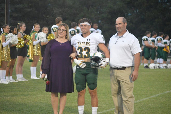 Menard linebacker Drew Lemoine (33, center) is flanked by his parents during the Eagles' senior night festivities Friday.