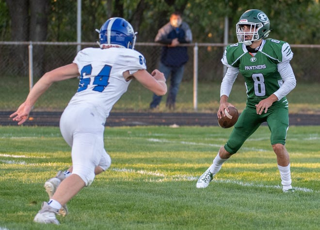 Pennfield's Ryne Petersen (8) looks for a reciver while Harper Creek's Hunter Stewart (64) applies pressure during first half action on September 18, 2020.