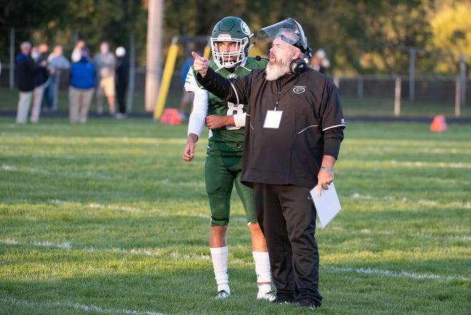 Pennfield's Ryne Petersen (8) discusses a play with head coach Mike Clothier during first half action against Harper Creek on September 18, 2020.