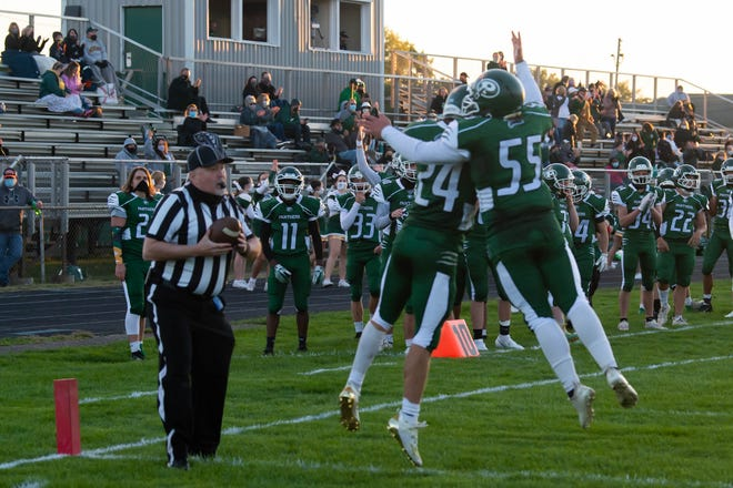 Pennfield's Cody Hultink (24) and Seth Clothier (55) celebrate after a touchdown against Harper Creek on September 18, 2020.