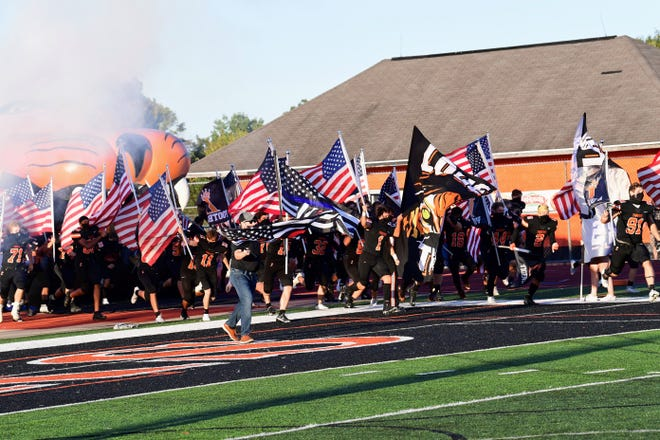 Loveland football team taking the field with USA flags and thin blue flag and thin red flag.