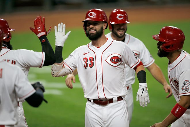 Cincinnati Reds designated hitter Jesse Winker (33) celebrates a three-run home run in the third inning of an MLB Interleague game between the Cincinnati Reds and the Chicago White Sox at Great American Ball Park in downtown Cincinnati on Friday, Sept. 18, 2020.
