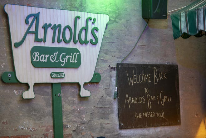 University of Cincinnati fans score a three-pointer by leaving a generous tip at Arnold's Bar and Grill on Saturday night. But Xavier is still in the lead.