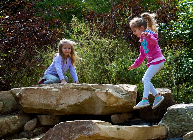 Isabella Adcox, left, watches as her sister Caidence Adcox, right, jumps off a rock as they explore the Nature Playscape in Wesselman Woods Friday morning, Sept. 18, 2020.