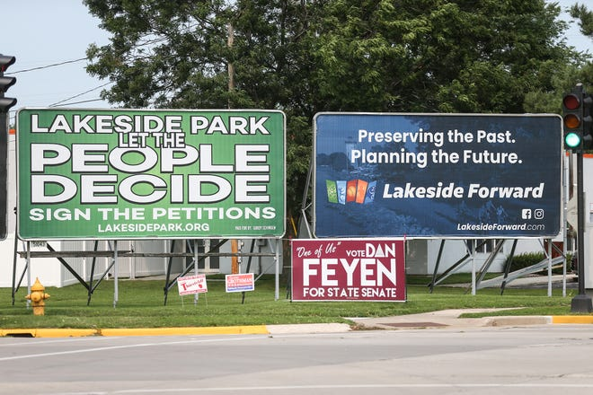 Billboards for and against proposed additions to the lighthouse peninsula in Lakeside Park are displayed  at the intersection of Park Avenue and Scott Street in Fond du Lac.