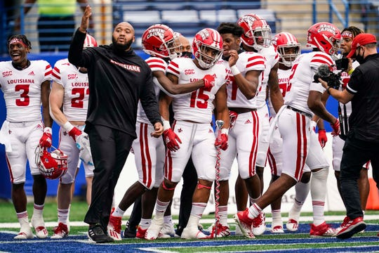 Louisiana-Lafayette players celebrate with running back Elijah Mitchell (15) after he scored the winning touchdown against the Georgia State.