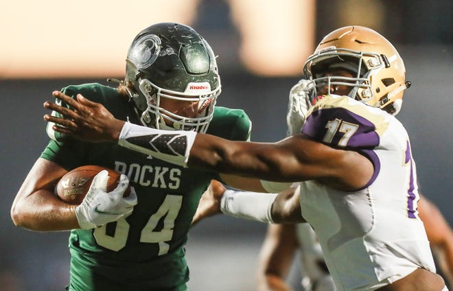 Trinity's Gavin Simpkins gives a stiff arm to Male's Elijah Manning as the Shamrocks routed the Bulldogs 43-14 Friday evening. Sept. 18, 2020