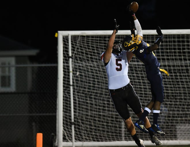 Grand Ledge senior Tre Welch, right, breaks up a pass intended for Adam Waszak of St. Johns, Friday, Sept. 18, 2020, during the season opener at Grand Ledge High School.
