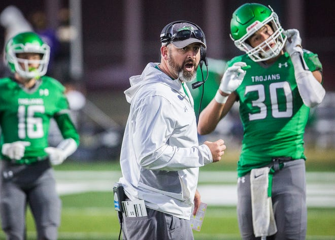 FILE -- New Castle football coach Kyle York leads the Trojans during the game against Yorktown at New Castle High School Friday, Sept. 18, 2020.