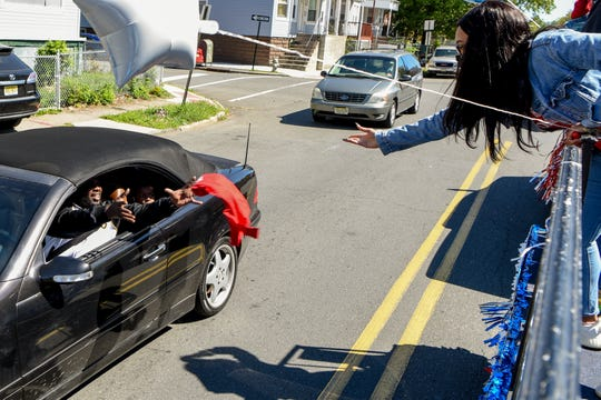 A census caravan travels around East Orange on Saturday September 19, 2020 to get the word out about completing the census. Ajah Baldwin tosses a t-shirt from the float to a man as he drives by.