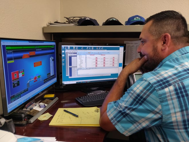 Nick Rios, Las Cruces Utilities SCADA senior system technician, monitors the installation of a valve at a well on the other side of town. LCU receives critical data to manage its operations through its monitoring system.