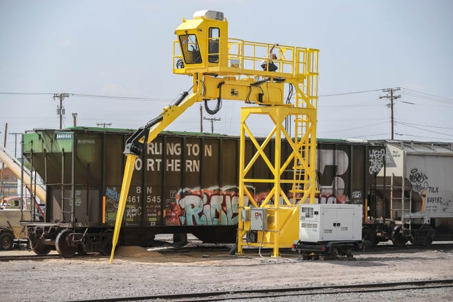 Workers learn to use a carhoe set up at BNSF Railway tracks parallel to Mesilla Street in Las Cruces on Friday, Sept. 18, 2020. The carhoe is used in lieu of sledgehammers or jackhammers to unload cattle feed. Residents are happier with the quieter solution.