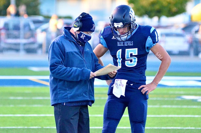 Richmond coach John Kocher and quarterback Jacob Ball go over plays against Armada during a Blue Water Area Conference football game on Sept. 18, 2020, at Richmond.