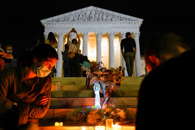 People gather at the Supreme Court Friday, Sept. 18, 2020, in Washington, after the Supreme Court announced that Supreme Court Justice Ruth Bader Ginsburg died of metastatic pancreatic cancer at age 87. (AP Photo/Alex Brandon)